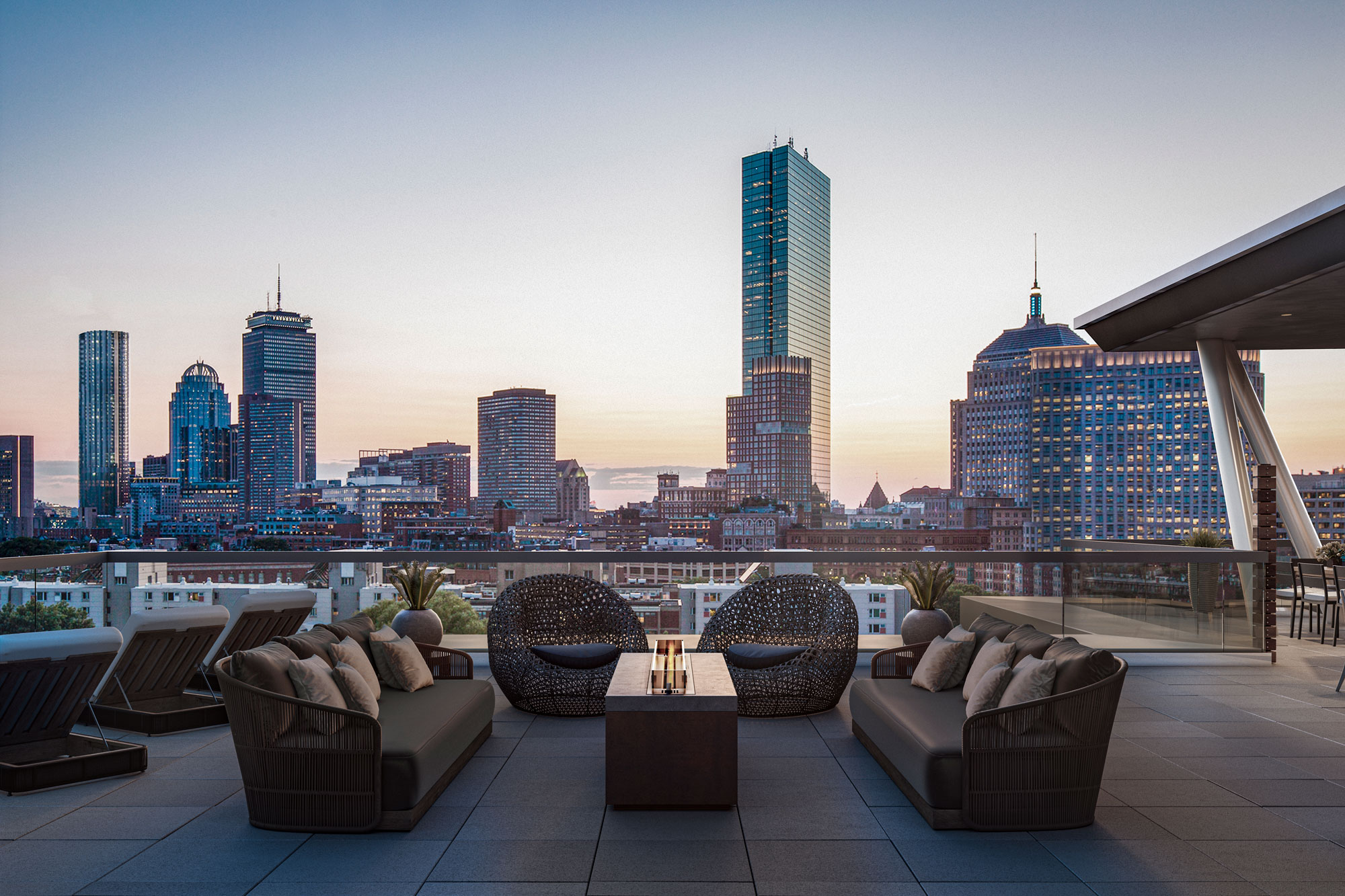Rooftop patio with couches and chairs overlooking downtown Boston