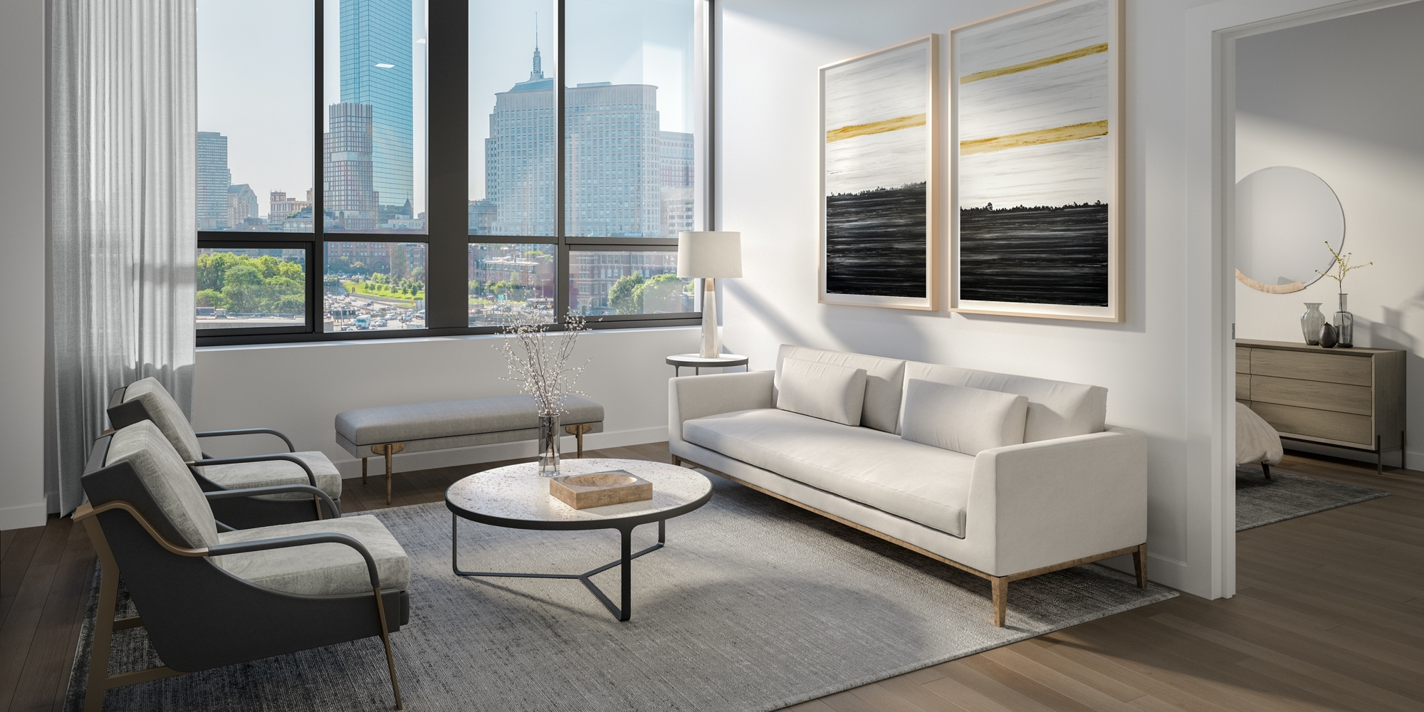 Living room of a 100 Shawmut unit with light-colored furniture and a view of downtown Boston