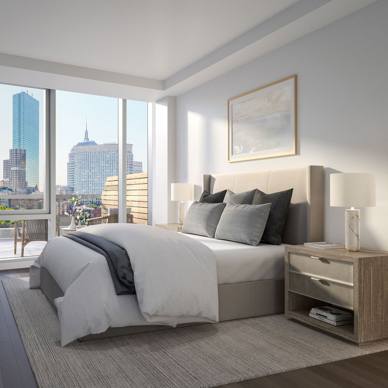Bedroom at 100 Shawmut with a full bed with white comforter and grey pillows overlooking Boston