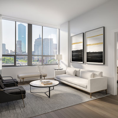 Living room of a 100 Shawmut unit with white couch and window overlooking downtown Boston